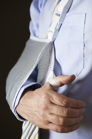 Man's arm in a shoulder sling following shoulder surgery.